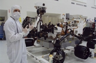 NASA engineer Matt Horner wearing a 'bunny suit.' He's standing in front of Curiosity, the next rover to head to Mars.