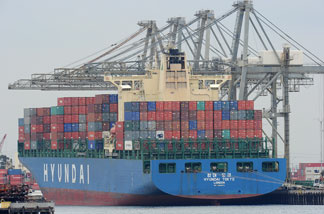 File photo: A container ship being unloaded is visible during the launch voyage of the Aquarium of the Pacific's new 'Urban Ocean' cruise, May 27, 2010 in San Pedro Bay off the coast of Los Angeles and Long Beach, California.