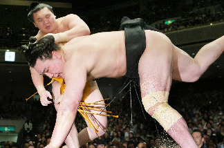 Mongolian-born grand champion, or yokozuna, Hakuho (top) throws his compatriot Harumafuji on the final day of the 15-day Summer Grand Sumo Tournament in Tokyo on May 23, 2010.