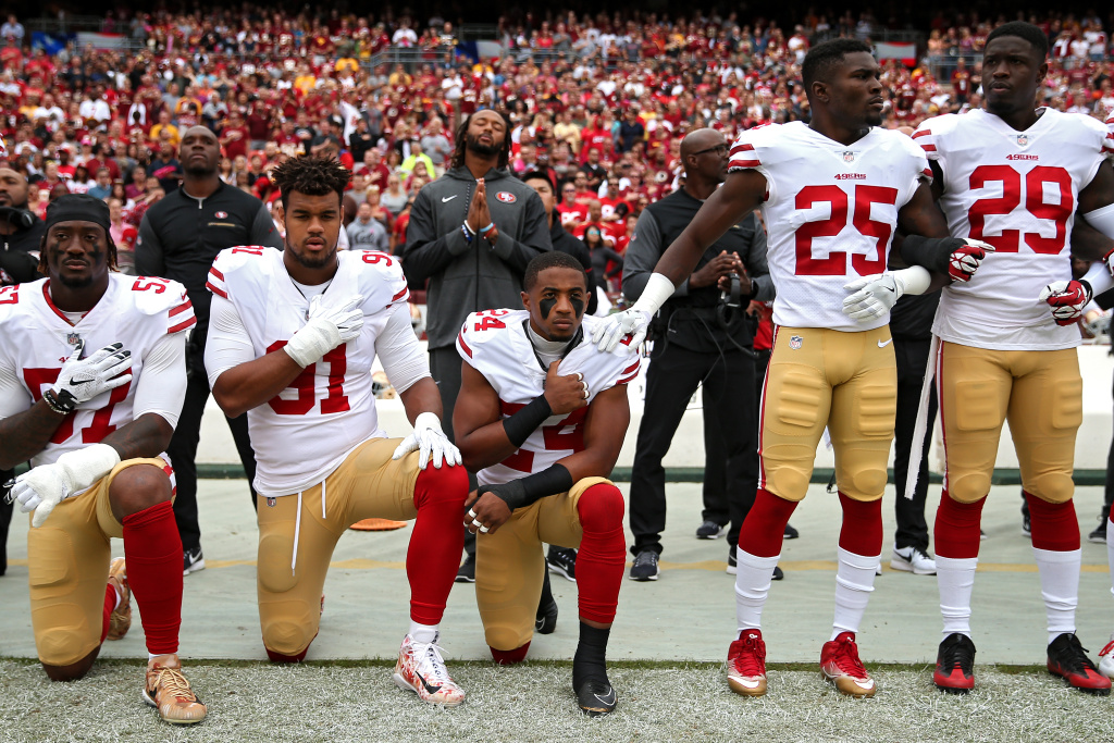 K'Waun Williams #24, Arik Armstead #91 and Eli Harold #57 of the San Francisco 49ers kneel while holding their hands over their chest during the national anthem before playing against the Washington Redskins at FedExField on October 15, 2017 in Landover, Maryland.