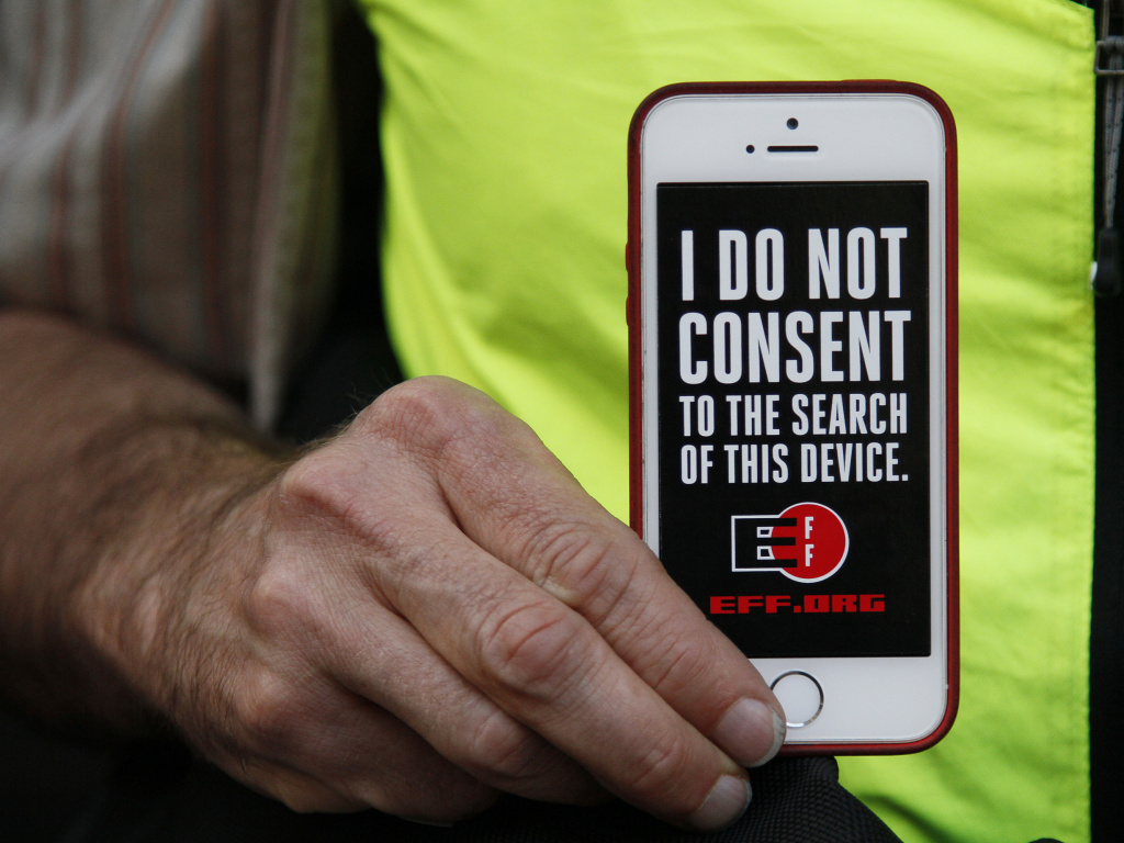 In this 2016 photo, a man holds up his iPhone during a rally in support of data privacy outside the Apple store in San Francisco. Watchdog groups that keep tabs on digital privacy rights are concerned that U.S. Customs and Border Protection agents are searching the phones and other digital devices of international travelers at border checkpoints in U.S. airports.