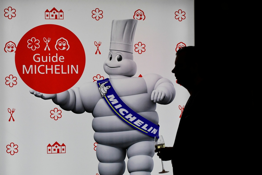 A man holds a glass of wine during the presentation of Germany's Michelin Guide 2017 in Berlin on December 1, 2016.