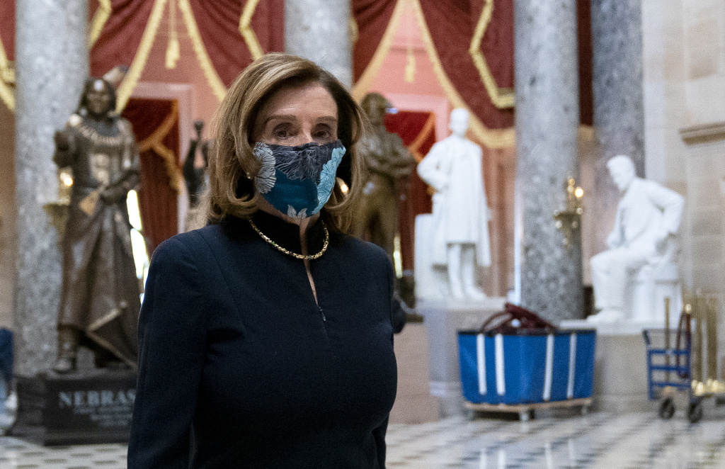 Speaker of the House Nancy Pelosi wears a protective mask while walking to her office from the House Floor on Wednesday.