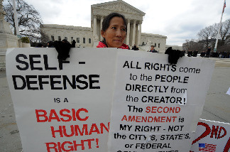 A demonstrator displays placards supporting a case on bearing arms in front of the Supreme Court in Washington, DC, on March 2, 2010.