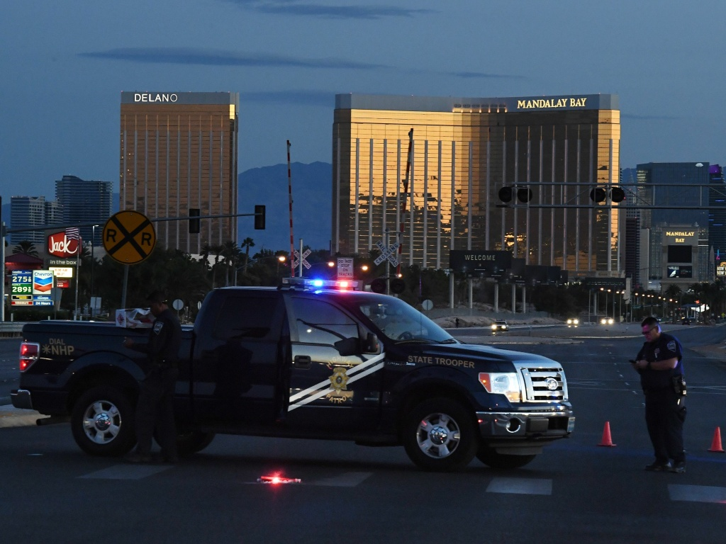Police form a perimeter around the road leading to the Mandalay Bay Resort and Casino after a gunman killed 59 people and injured more than 500 others when he opened fire Sunday night on a country music concert in Las Vegas.