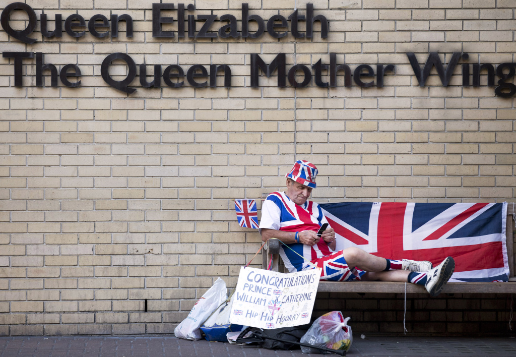 Royal supporter Terry Hutt sits on a bench looking at his mobile phone in front of the Queen Elizabeth, The Queen Mother Wing, directly opposite The Lindo Wing of Saint Mary's Hospital in London on July 10, 2013. Prince William and his wife Catherine's baby, which will be third in line to the throne, will be born in the private Lindo wing of St Mary's Hospital, where William was born in 1982 and his brother Harry in 1984. AFP PHOTO / JUSTIN TALLIS (Photo credit should read JUSTIN TALLIS/AFP/Getty Images)