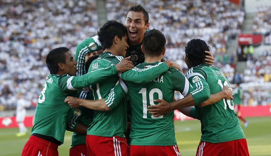 Mexico's players celebrate a goal against New Zealand during their World Cup qualifying football match in Wellington on November 20, 2013. Mexico won 4-2.