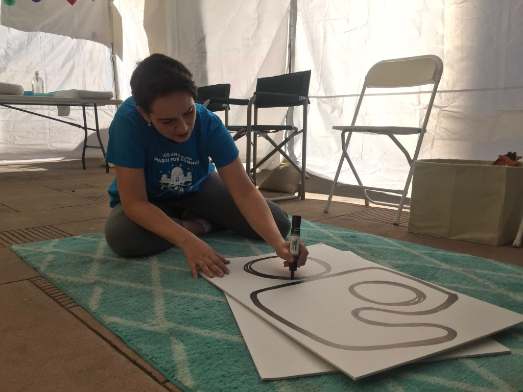 Veronica Galen draws the International Breastfeeding Symbol on a sign for the family tent she organized for the March for Science in L.A. on April 14, 2018.