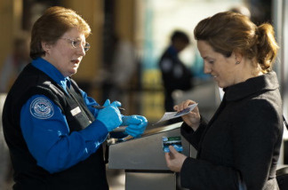 An airline passenger has her boarding pass and identification papers reviewed by a TSA Officer(L) at a security checkpoint inside Ronald Reagan Washington National Airport