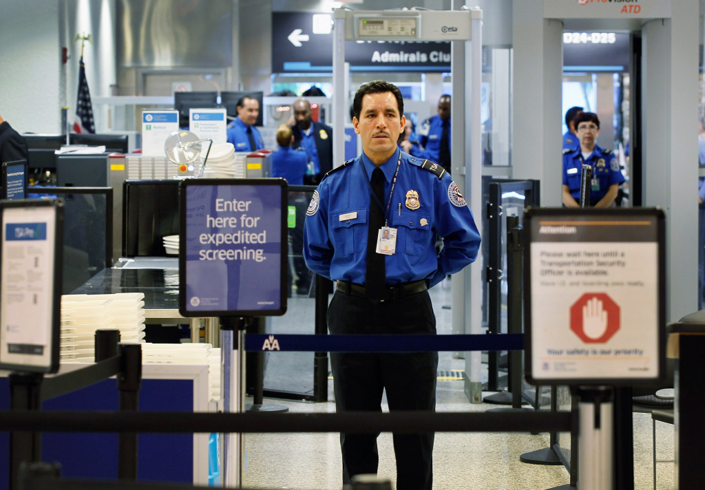 A TSA agent waits for passengers to use the TSA PreCheck lane being implemented by the Transportation Security Administration at Miami International Airport on October 4, 2011.