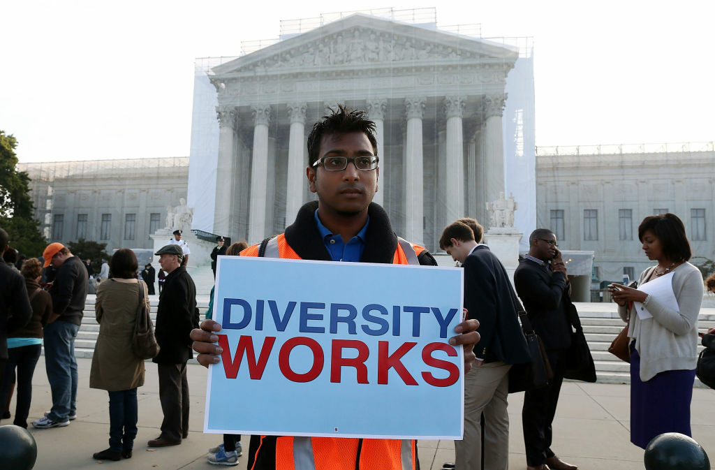Travis Ballie holds a sign that reads (Diversity Works) in front of the U.S. Supreme Court on October 10, 2012 in Washington, DC. Today the high court is scheduled to hear arguments on Fisher v University of Texas at Austin, and are tasked with ruling on whether the university's consideration of race in admissions is constitutional.