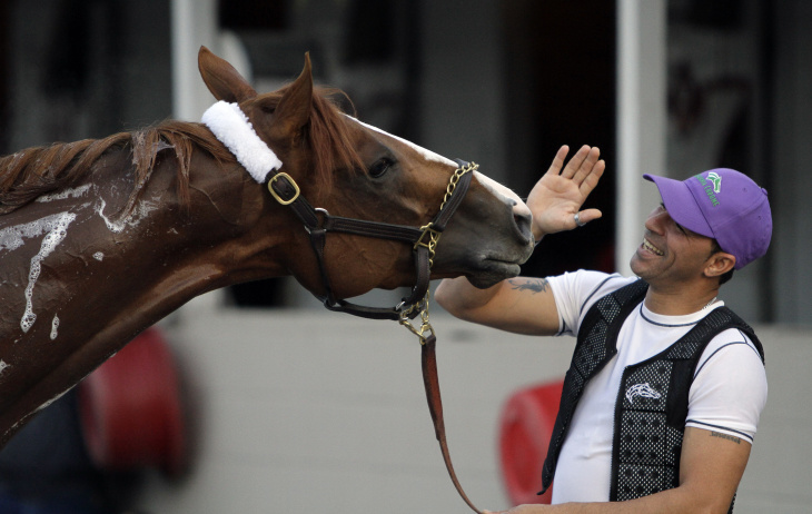Exercise rider William Delgado takes Kentucky Derby entrant California Chrome for a morning workout during a morning workout at Churchill Downs Friday, May 2, 2014, in Louisville, Ky.