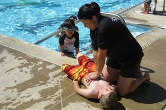 Lynnette Round of the Orange County Fire Authority demonstrates CPR on her son during a mock drowning exercise in Irvine.