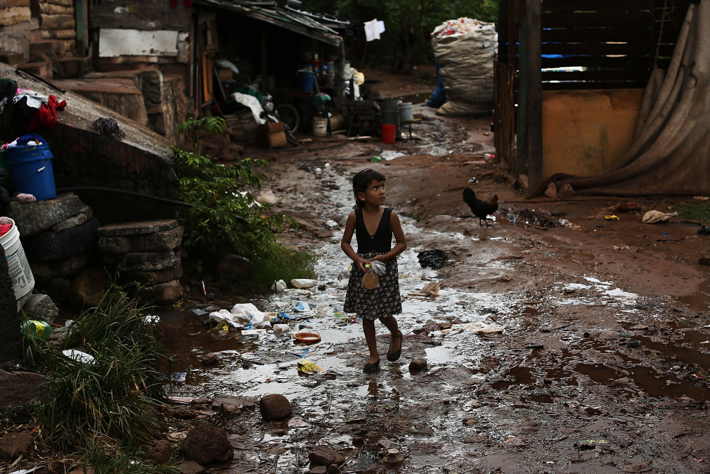 A young child walks home in an area known for heavy drug dealing on July 18, 2012 in Tegucigalpa, Honduras. Honduras now has the highest per capita murder rate in the world and its capital city, Tegucigalpa, is plagued by violence, poverty, homelessness and sexual assaults. With an estimated 80% of the cocaine entering the United States now being trans-shipped through Honduras, the violence on the streets is a spillover from the ramped rise in narco-trafficking. The non-governmental organization Doctors Without Borders has set up a program in the capital that looks to provide medical and psychological care to the homeless population. Each day a team goes out into the streets to meet with vulnerable groups of homeless to assess their needs.