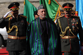 Afghan President Hamid Karzai (C) passes an honour guard as he arrives for his swearing in ceremony as the country's president for another five years at the Presidential Palace in Kabul on November 19, 2009.