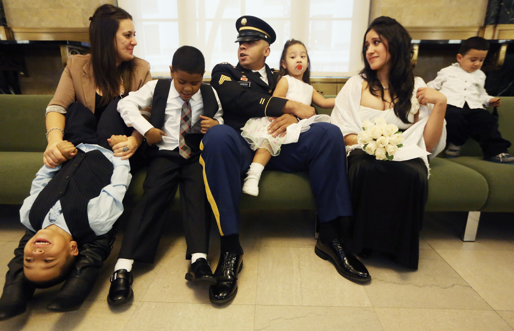 (L-R) Jennie Mallozzi holds Steven Capistran, Michael Ganney, U.S. Army Sgt. Jamie Vargas holds daughter Hailey Vargas, soon-to-be wife Bernice Vargas and Tyler Capistran look on at the Manhattan Marriage Bureau inside the Office of the City Clerk as they await the Vargas wedding ceremony on October 26, 2012 in New York City.