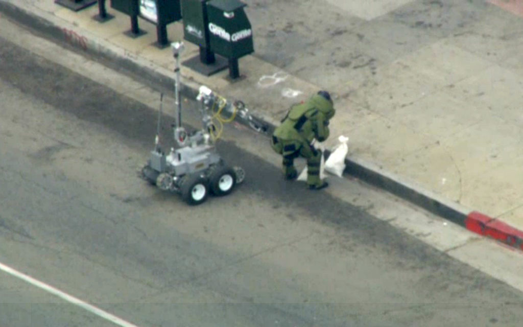 A bomb squad robot and a member of the squad outside an East L.A. bank on Wednesday, Sept. 5, 2012.