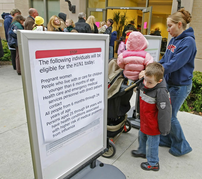 A young boy looks at a sign as he and his mother arrive to wait in line with several thousand other people at the Utah County Health Department to get H1N1 vaccine shots October 27, 2009 in Provo, Utah. After health department got a shipment of 4000 vaccines overnight, a large line formed with a wait of four to five hours.