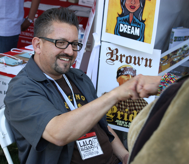 "Lalo Alcaraz, creator of the first nationally-syndicated, politically-themed Latino daily comic strip, ""La Cucaracha"", greets a fan at his booth."