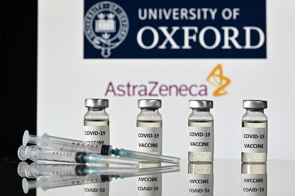An illustration picture shows vials with Covid-19 Vaccine stickers attached and syringes, with the logo of the University of Oxford and its partner British pharmaceutical company AstraZeneca, on November 17, 2020.