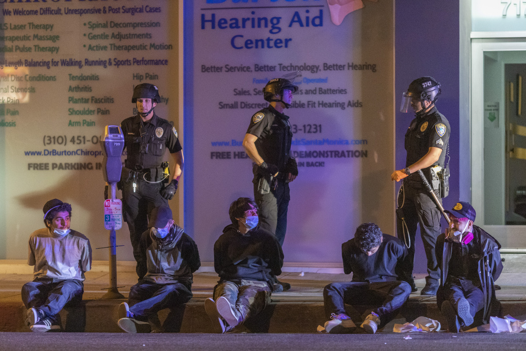 People sit in handcuffs under arrest during an emergency curfew during demonstrations following the death of George Floyd on May 31, 2020 Santa Monica, California.