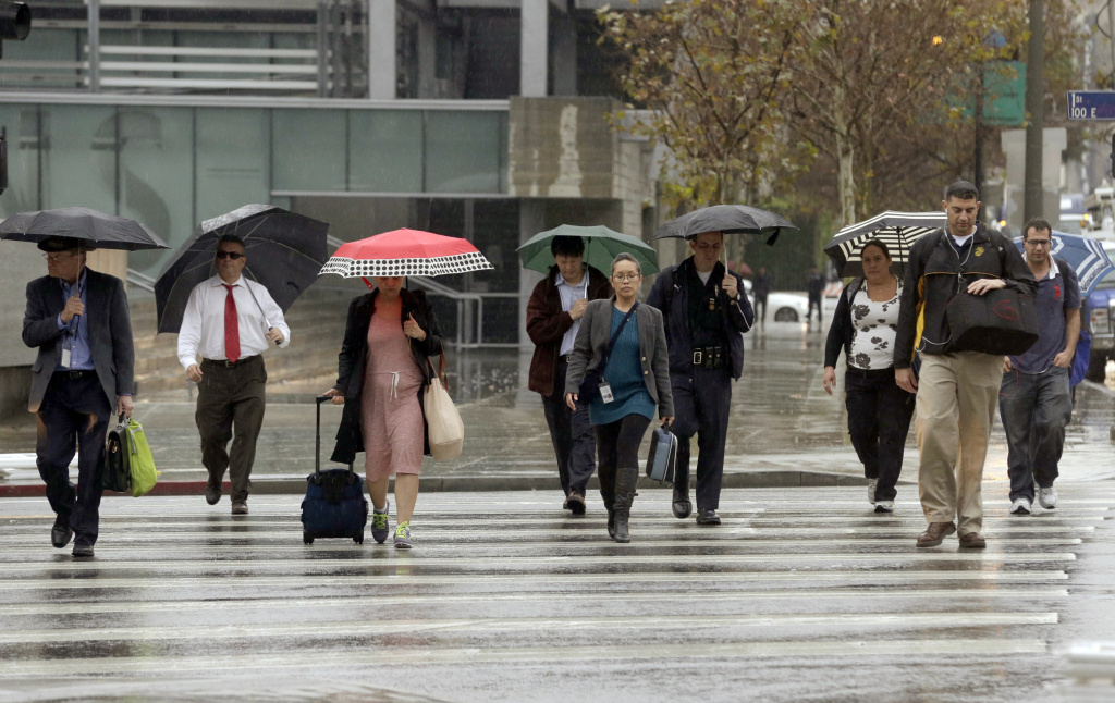 Commuters walk under a light rain in downtown Los Angeles on Feb. 17, 2016, as a storm system arriving in California ended days of clear skies, blazing sunshine and record-setting heat.