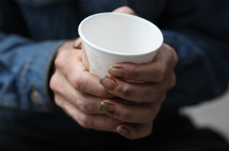 A homeless man holds a cup as he asks for spare change.