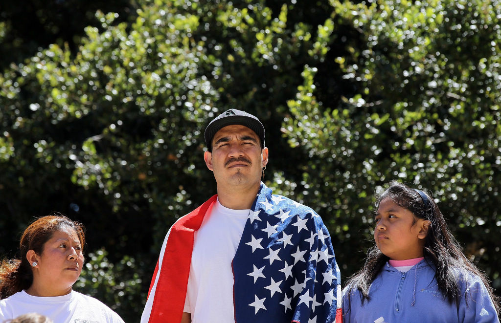 A man wears an American flag as he protests Arizona's new immigration law during a rally at Oakland City Hall April 30, 2010 in Oakland, California.