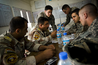 An Iraqi army officer talks to U.S. soldiers during an exchange of intelligence June 2 at an Iraqi army base near Al Guwair, south of Mosul, Iraq.