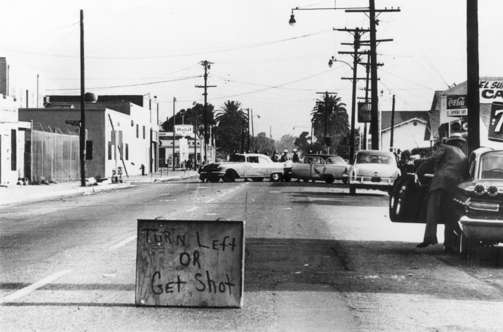 Armed National Guardsmen march toward smoke on the horizon during the street fires of the Watts riots, Los Angeles, California, August 1965