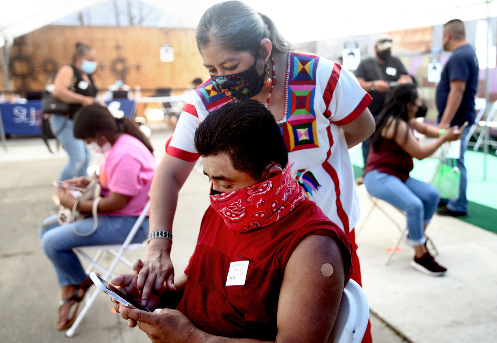 Volunteer Miriam Lopez Ambrosio (TOP), a folkloric dancer from Oaxaca, assists a person with their second vaccination appointment on their phone at a clinic targeting Central American Indigenous residents at CIELO, an Indigenous rights organization, on April 10, 2021 in Los Angeles, California.