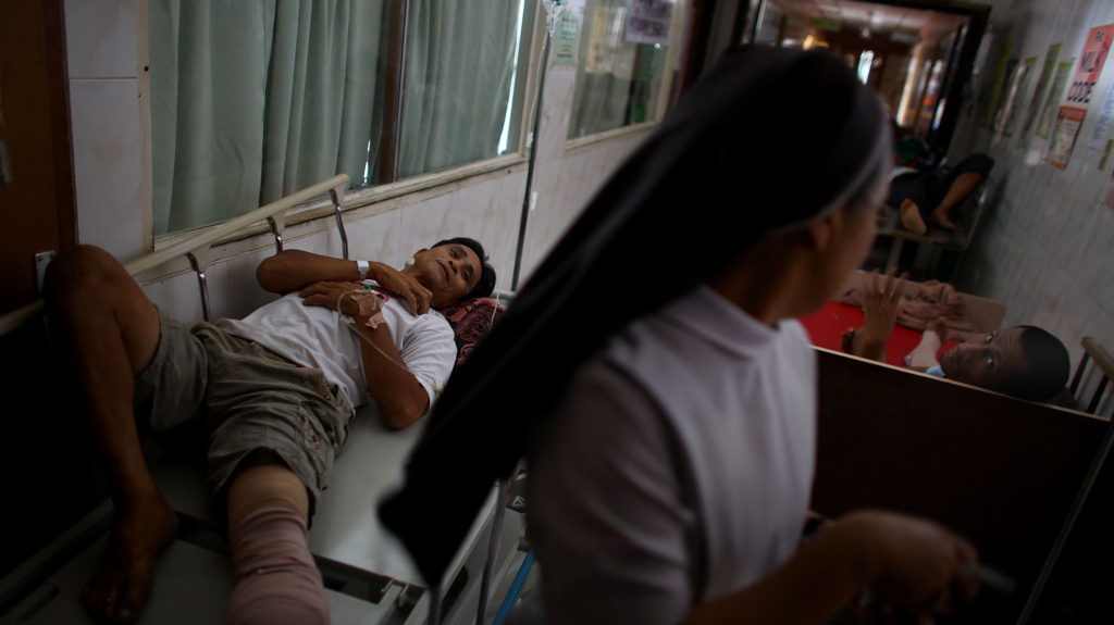 Patients injured during Typhoon Haiyan lie in the halls of the Divine Word Hospital in Tacloban, the Philippines. Despite severe damage to the ground floor and the loss of the roof, the staff of the hospital keep treating patients.