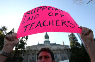 A demonstrator holds a sign during a Pink Friday protest March 13, 2009 at the Berkeley Unified School District building in Berkeley, California. Teachers, students and parents were protesting billions of dollars in proposed budget cuts to education that threaten more than 26,500 across the state with pink slips.