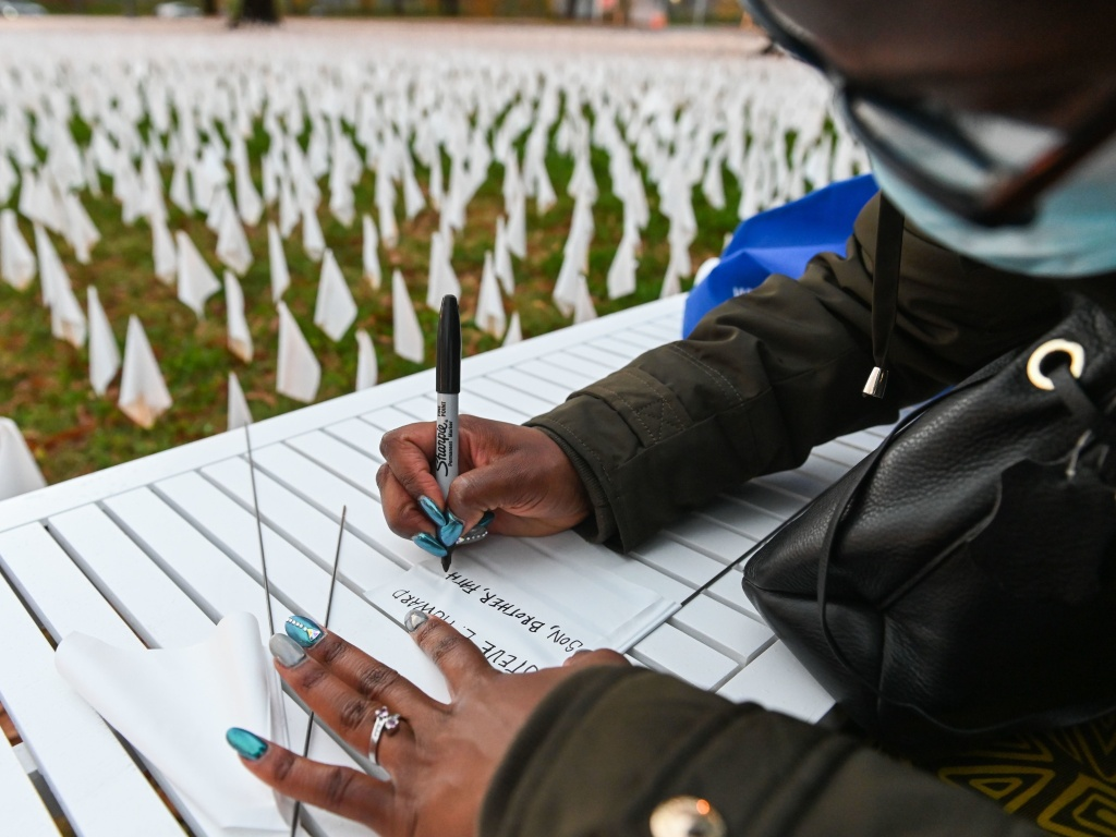 Patrice Howard writes on white flags before planting them to remember her recently deceased father and close friends in November at