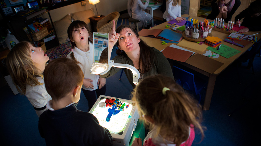 Using a projector, Jodi Doyle points out shadows on the ceiling to students in her preschool class at the Eliot School in Boston. Boston has become a beacon for the universal preschool movement, but so far it can only provide seats for about half the interested families.