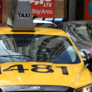 A Lyft car drives next to a taxi on June 12, 2014 in San Francisco, California. The California Public Utilities Commission is cracking down on ride sharing companies like Lyft, Uber and Sidecar by issuing a warning that they could lose their ability to operate within the state if they are caught dropping off or picking up passengers at airports in California.