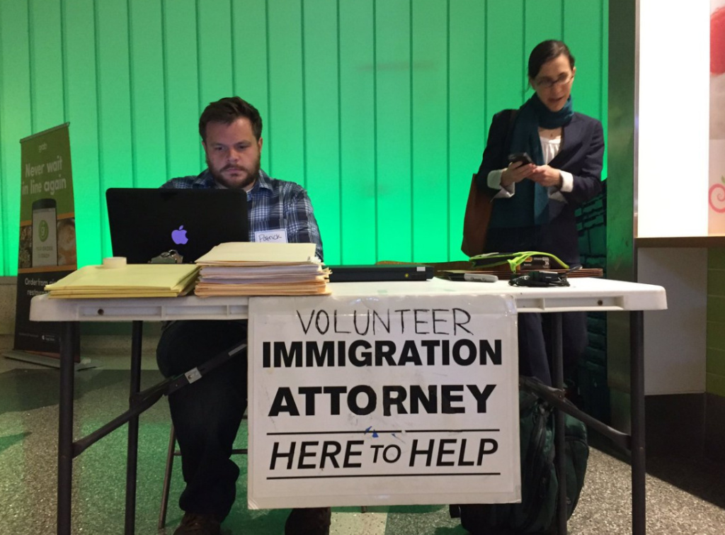 Patrick Fodell, training coordinator at OneJustice, left, and Talia Inlender, a senior staff attorney with Public Counsel, prepare to answer questions from travelers and relatives in the wake of the release of President Trump's latest travel ban at the Tom Bradley International Terminal at LAX on Monday, March 6, 2017.