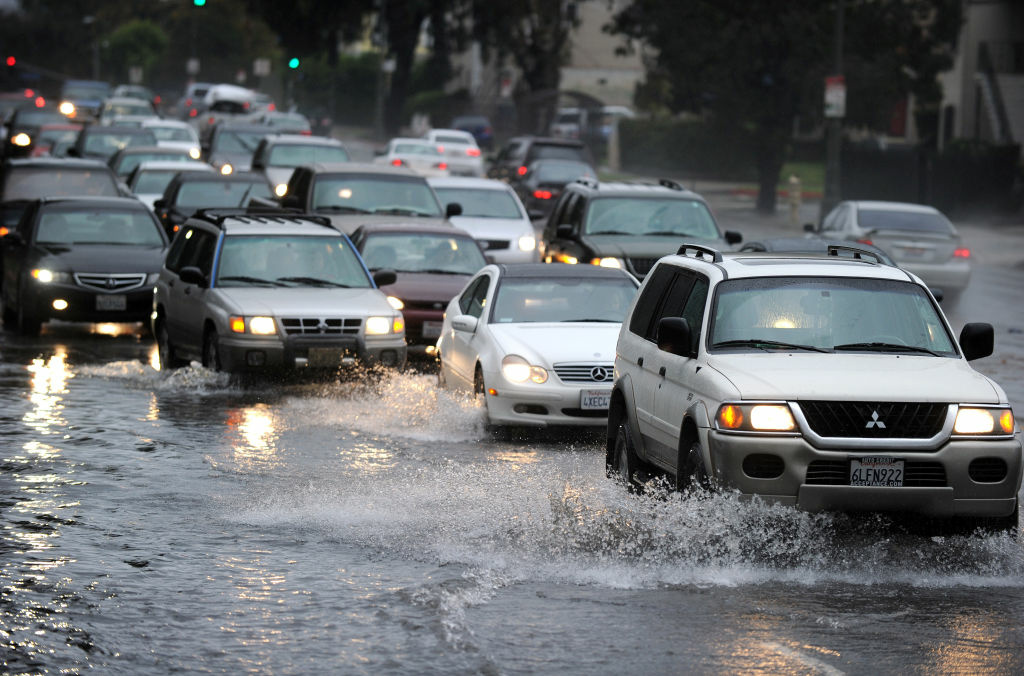 People drive their cars through deep water in Los Angeles, California, on December 22, 2010. Downtown Los Angeles received one-third of its annual average rainfall in less than a week. As of midmorning yesterday, the rain gauge at the University of Southern California campus recorded 5.77 inches.