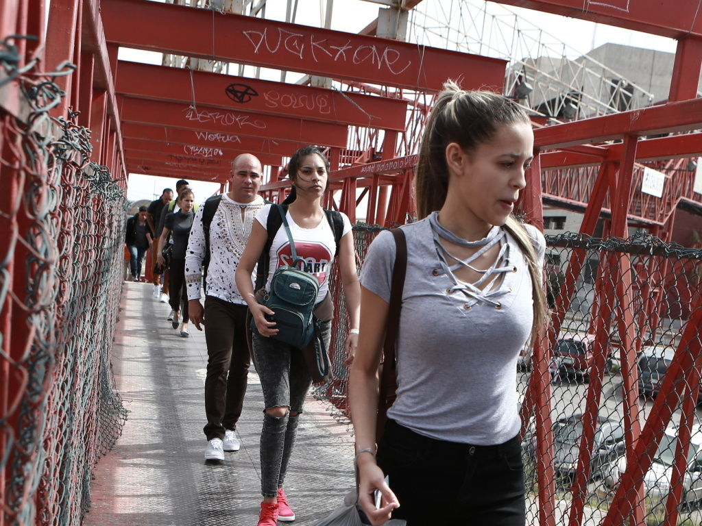 Cuban migrants are escorted by Mexican immigration officials in Ciudad Juarez, Mexico, in April, as they cross the Paso del Norte International bridge to be processed as asylum seekers on the U.S. side of the border.
