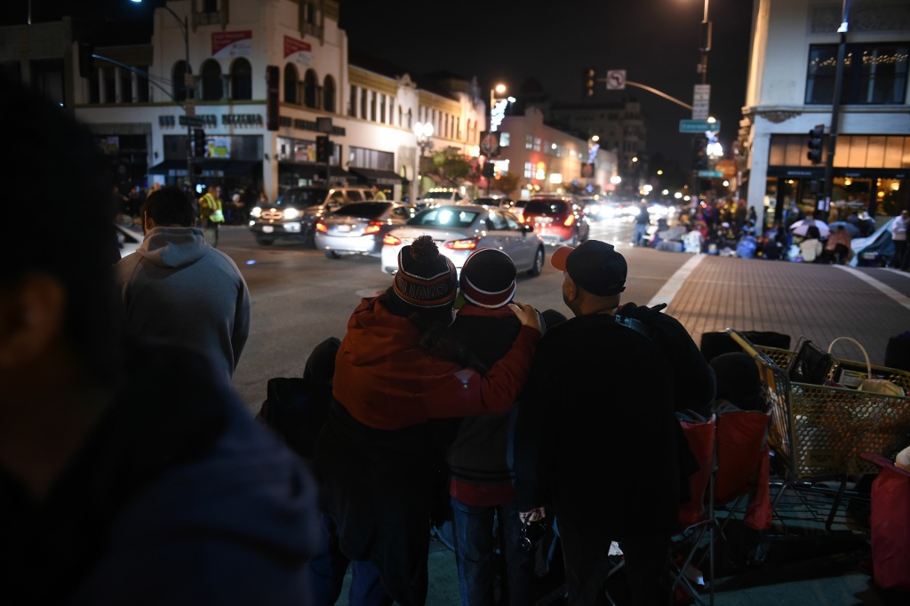 People line the streets as they await the start of the 128th Rose Parade in Pasadena, California, January 2, 2017.
