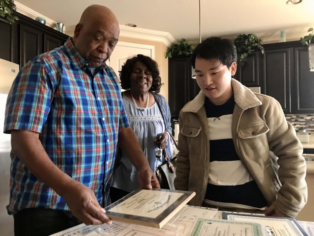 Seojun Lee (right) looks over some of his school and ROTC documents with his ROTC instructor, retired Army Lt. Col. James Gardner and Gardner's partner, Beverly Meeks.