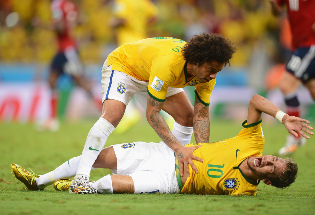 Neymar of Brazil lies injured while Marcelo of Brazil shows concern during the 2014 FIFA World Cup Brazil Quarter Final match between Brazil and Colombia at Estadio Castelao on July 4, 2014 in Fortaleza, Brazil.