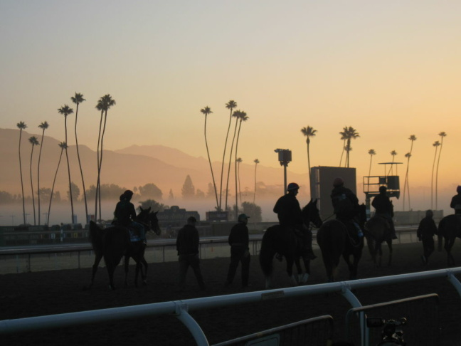 The sun begins to rise at Santa Anita Park as riders exercise their horses.