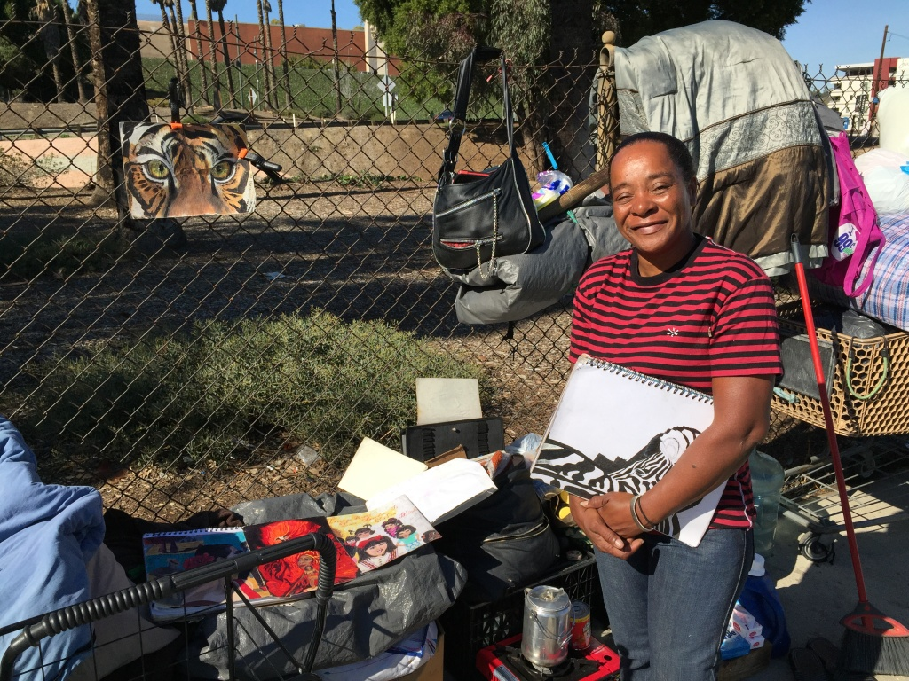 Skid row resident and artist Juanita Pina stands with some of her drawings