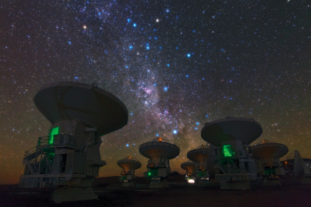 """ESO Photo Ambassador Babak Tafreshi snapped this remarkable image of the antennas of the Atacama Large Millimeter/submillimeter Array (ALMA), set against the splendour of the Milky Way. The richness of the sky in this picture attests to the unsurpassed conditions for astronomy on the 5000-metre-high Chajnantor plateau in Chile's Atacama region.  This view shows the constellations of Carina (The Keel) and Vela (The Sails). The dark, wispy dust clouds of the Milky Way streak from middle top left to middle bottom right. The bright orange star in the upper left is Suhail in Vela, while the similarly orange star in the upper middle is Avior, in Carina. Of the three bright blue stars that form an """"L"""" near these stars, the left two belong to Vela, and the right one to Carina. And exactly in the centre of the image below these stars gleams the pink glow of the Carina Nebula (eso1208).  ESO, the European partner in ALMA, is providing 25 of the 66 antennas that will make up the completed telescope. The two antennas closest to the camera, on which the careful viewer can find the markings """"DA-43"""" and """"DA-41"""", are examples of these European antennas. Construction of the full ALMA array will be completed in 2013, but the telescope is already making scientific observations with a partial array of antennas.  Babak Tafreshi is founder of The World At Night, a programme to create and exhibit a collection of stunning photographs and time-lapse videos of the world's most beautiful and historic sites against a night-time backdrop of stars, planets and celestial events.  ALMA, an international astronomy facility, is a partnership of Europe, North America and East Asia in cooperation with the Republic of Chile. ALMA construction and operations are led on behalf of Europe by ESO, on behalf of North America by the National Radio Astronomy Observatory (NRAO), and on behalf of East Asia by the National Astronomical Observatory of Japan (NAOJ). The Joint ALMA Observatory (JAO) provides the uni"""