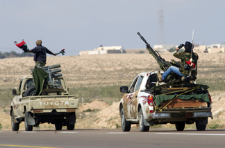 Rebel fighters drives towards the university (background) of the key old port of Brega on their way to battle against loyalist troops on April 4, 2011.