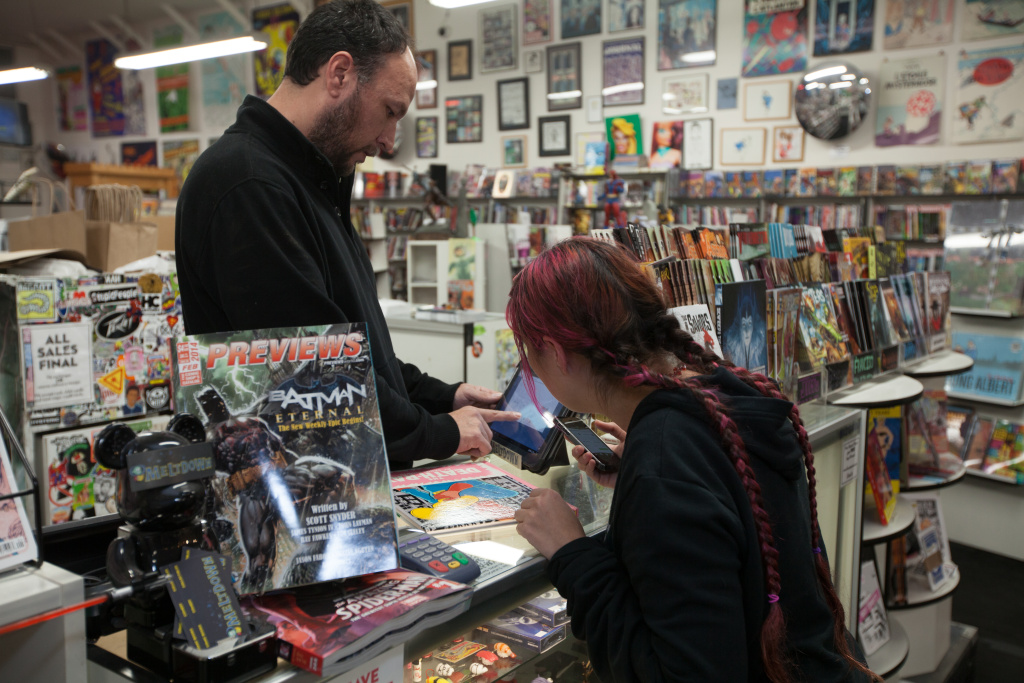 Meltdown Comics' store manager tallies up a Bitcoin order using a Bitcoin merchant application on Thursday, Jan. 30, 2014.