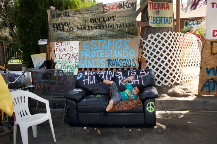 Adrian Hernandez plays outside his foreclosed house in Van Nuys. Occupy San Fernando Valley started camping out in the house on August 26th, 2012.