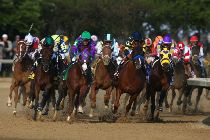 California Chrome #5, ridden by Victor Espinoza, crosses the finish line to win the 140th running of the Kentucky Derby at Churchill Downs on May 3, 2014 in Louisville, Kentucky.