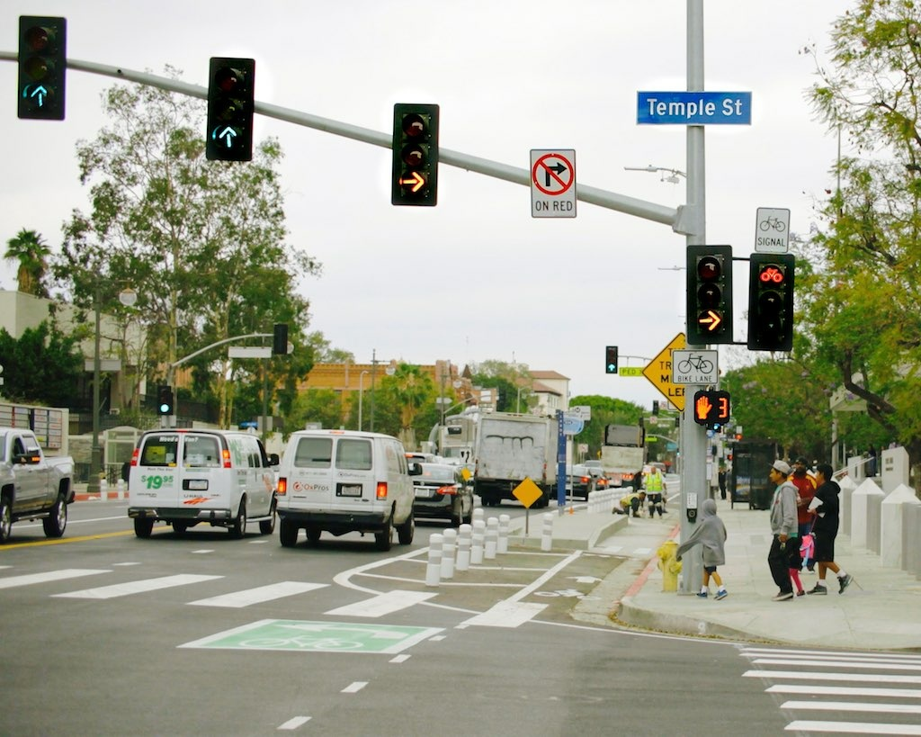 "Flashing yellow right turn signals for drivers are seen along with a red bike signal at the intersection of Los Angeles and Temple streets in downtown L.A. A ""transit island"" for bus riders and plastic bollards that mark the left side of a protected bike lane can also be seen in the distance."